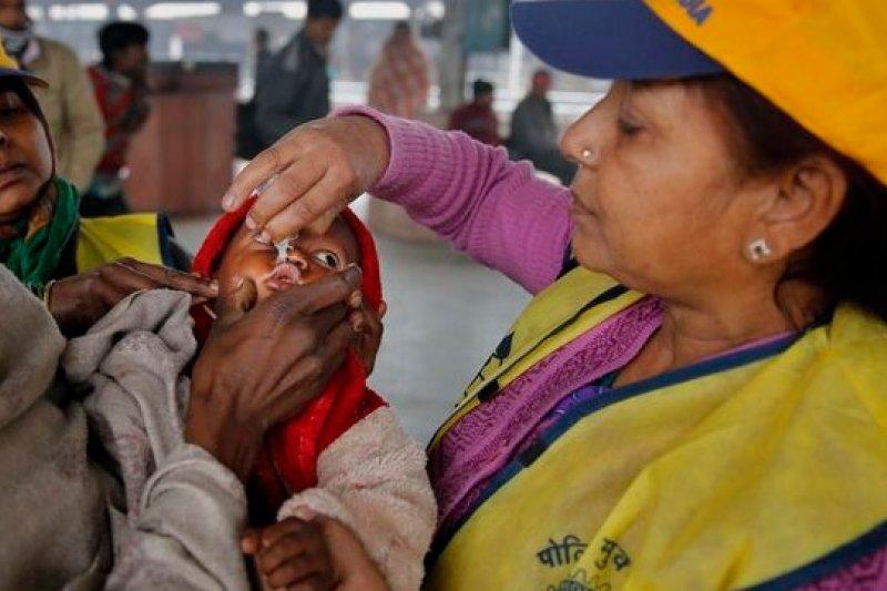 印度公衛人員為幼童施打口服小兒麻痺疫苗。(美聯社)