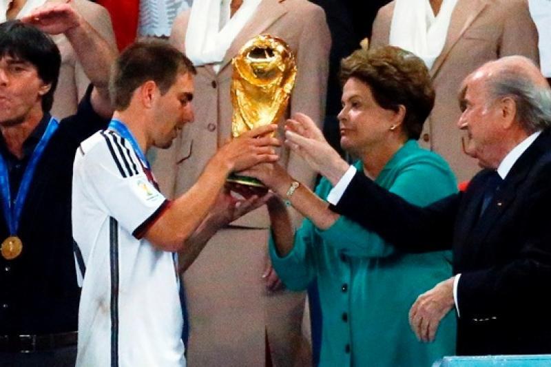德國隊長拉姆(Philipp Lahm)(左二)自巴西總統羅塞芙(右二)及國際足總主席布拉特(Sepp Blatter)(右一)手中接過冠軍獎盃(美聯社)
