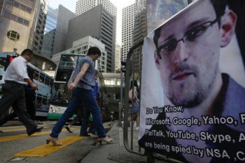 史諾登事件發生後,與美國政府合作的九家大型網路、電訊公司名字被張貼在香港的商業區。(美聯社)