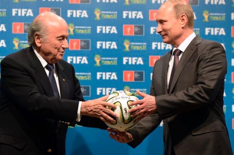 俄羅斯總統普京(右)從FIFA主席布拉特手中接過足球,象徵俄羅斯正式接下2018年世界盃主辦權。(美聯社)