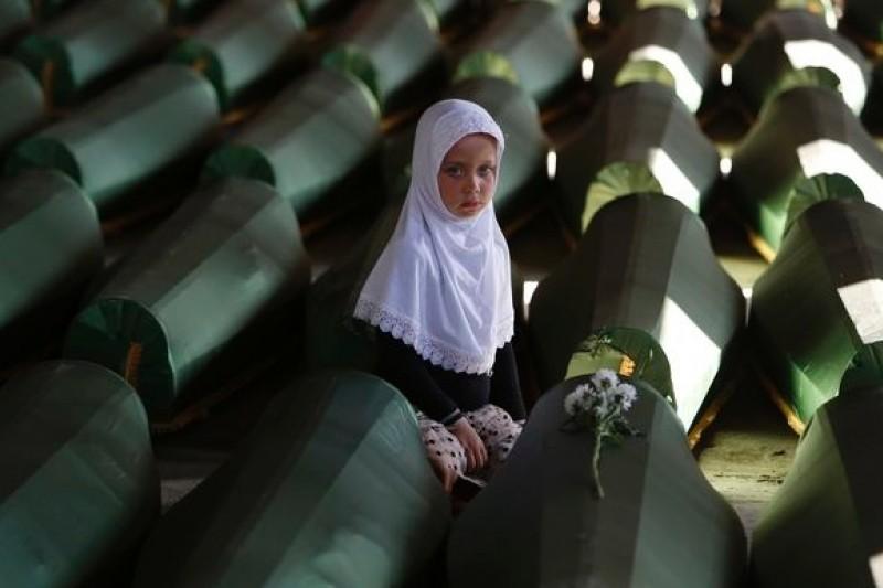 波士尼亞克族的小女孩與大屠殺罹難者的棺木(美聯社)
