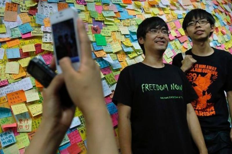 香港特區政府和學聯代表即將在10日啟動談判,但香港未來幾年的發展難一團紛亂。(圖為學聯領袖周永康和黃之鋒在致家長信牆前/美聯社)