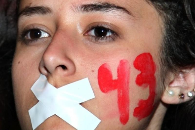 一名示威女子以膠布封口,臉上寫上失蹤學生數目43,表達對學生長期下落不明的不滿(美聯社)