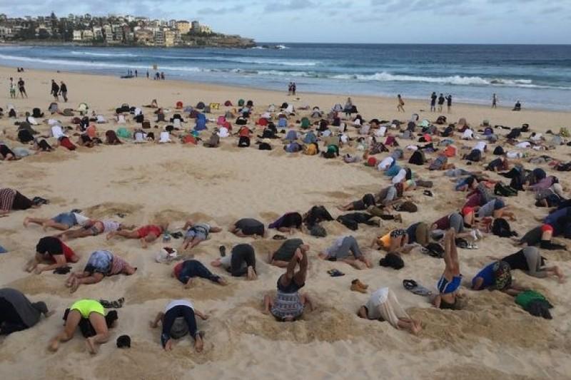 一群民眾13日聚集在雪梨的邦迪海灘,將頭埋入沙中,抗議澳洲政府對全球暖化危機視而不見。(取自網路)