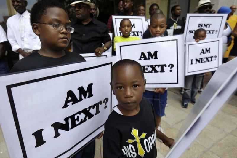 美國密州佛格森鎮的黑人小孩舉著標語抗議當地警方執法過當。(美聯社)