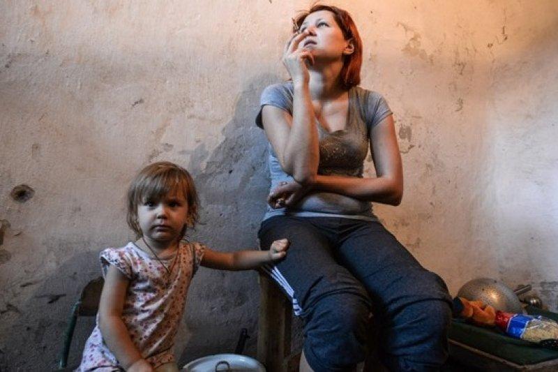 一名孩童與母親躲藏在烏克蘭東部的一個防彈掩蔽處(美聯社)