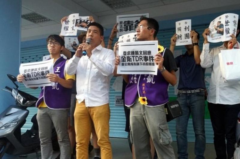 台北市議員參選人、社運人士王奕凱20日號召支持者前往尚未開幕的連勝文競選總部前,要求連勝文公開持股。(蘇仲泓攝)