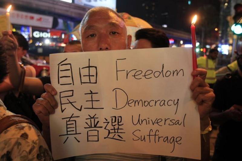 香港佔中民眾29日拿著紙板,寫著自由民主真普選。(美聯社)