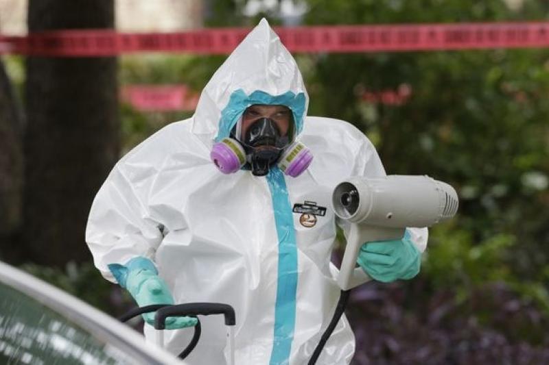 德州公衛人員全副防護裝,在染病護士住處外進行消毒。(美聯社)