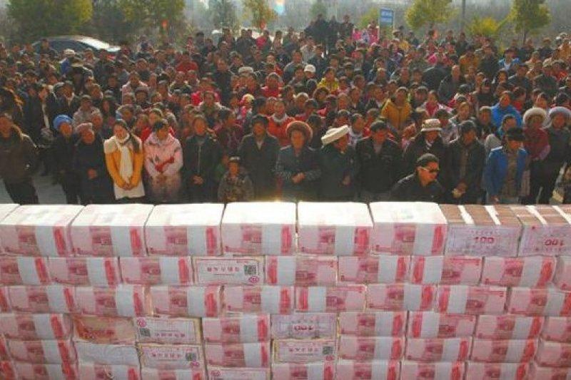 四川涼山一處農村合作社分紅,現金堆成的「錢牆」壯觀。(取自網路)