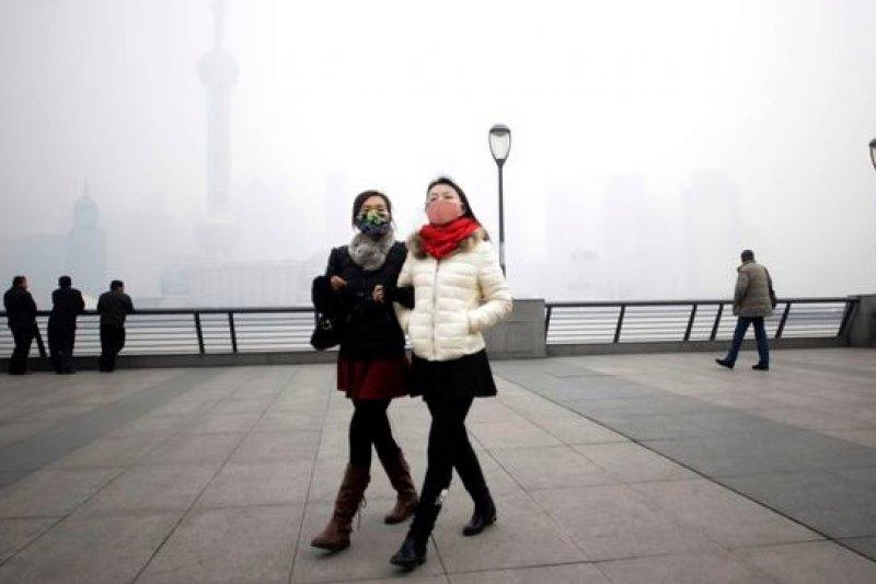 兩名遊客帶著口罩遊上海,避免髒空氣傷身(美聯社)