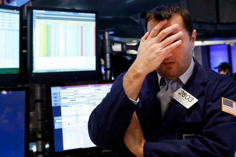 新興市場爆發危機,重創24日的歐美股市,紐約證券交易所一名交易員只能掩面歎息。(美聯社)