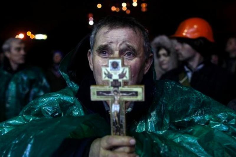 在基輔的獨立廣場上,一名反政府示威民眾手持十字架急切念禱(美聯社)