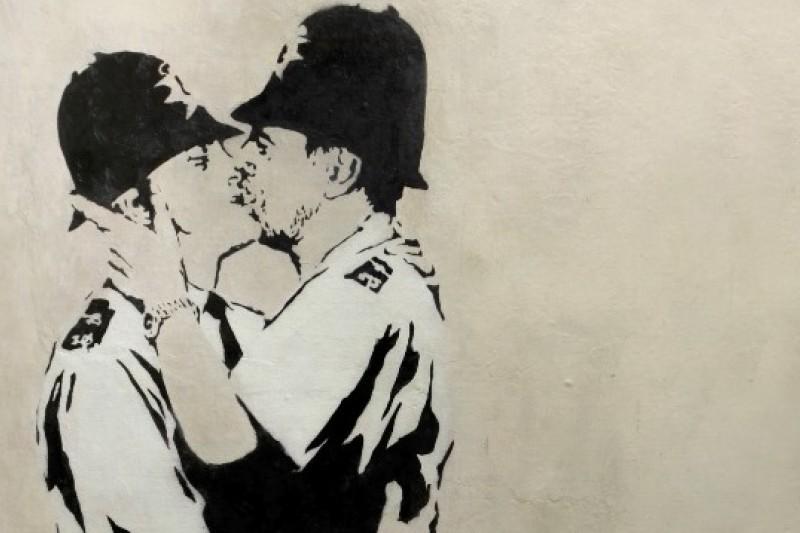 英國藝術家班克斯的作品《接吻的警察》於18日以57萬5千美元的價格賣出(美聯社)