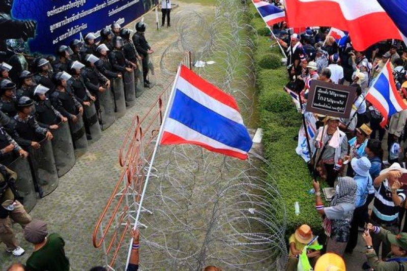 泰國示威群眾(右)包圍總理穎拉臨時辦公室,與泰警(左)對峙。(美聯社)