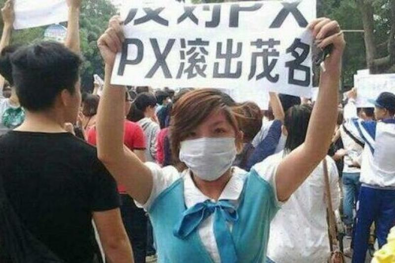 廣東茂名民眾手持標語,要求「PX項目滾出茂名」。(取自網路)