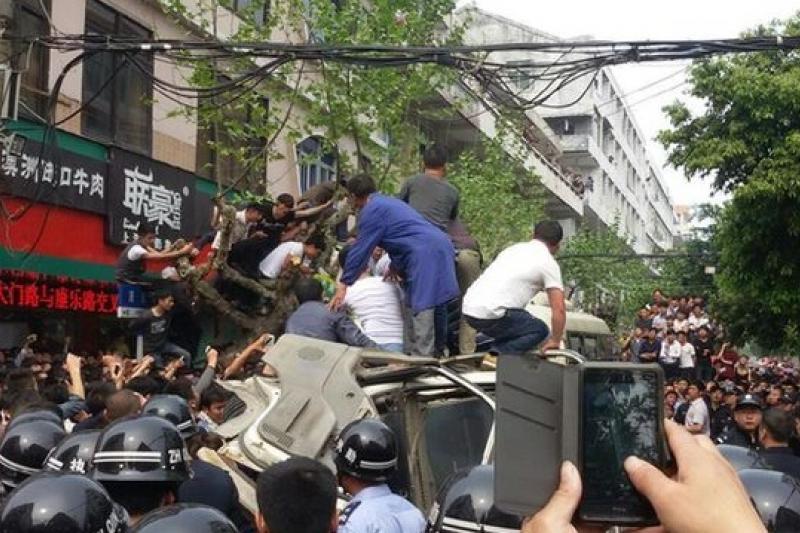 民眾將打人城管的麵包車團團包圍,警方第一時間也無法勸離。(取自網路)