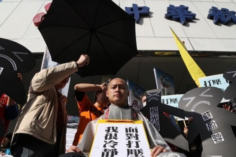 華航工會第3分會與機師工會29日於華航台北分公司再度展開抗爭,受停飛處分的空服員張書元以落髮行動表達對華航最沉痛的抗議,並撐起傘象徵「無法無天」。(楊子磊攝)