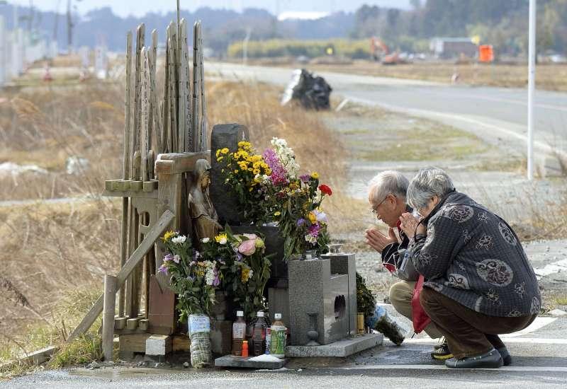 兩位老人家在3月11日回到福島縣災區,祭拜4年前不幸在311震災中逝世的親人。(美聯社)