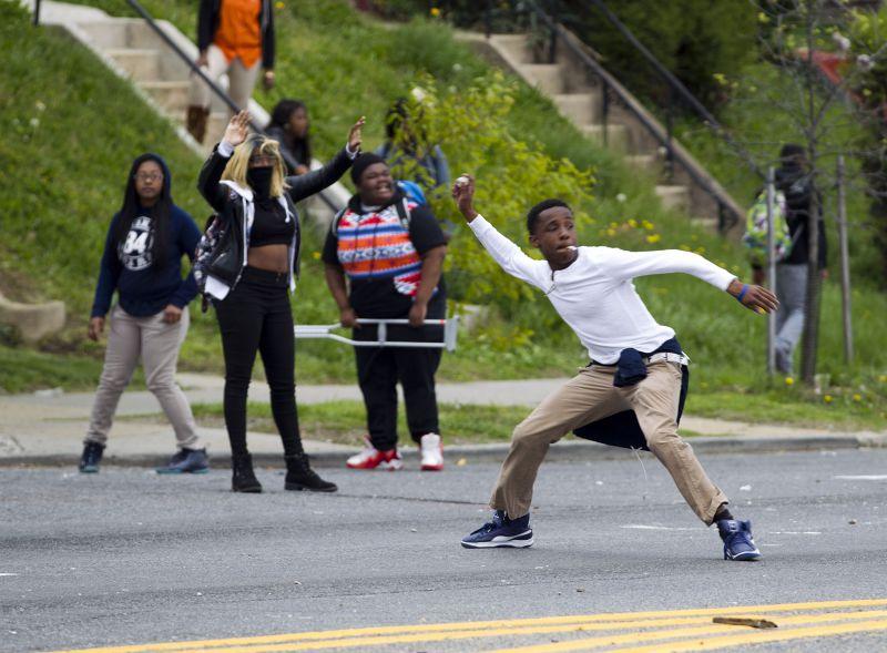 巴爾的摩民眾朝警方丟擲石塊。(美聯社)