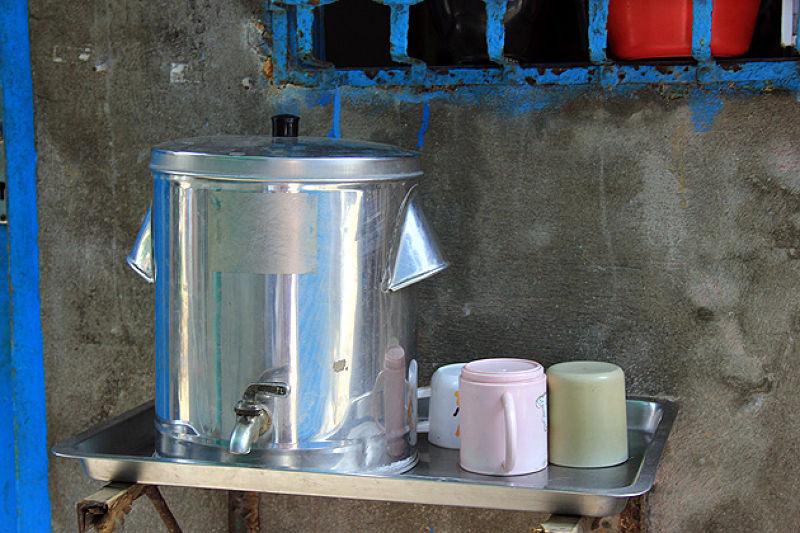 山峽的小巷弄裡,屋前放著小鐵桶,奉茶給過路客飲用。(圖/作者)
