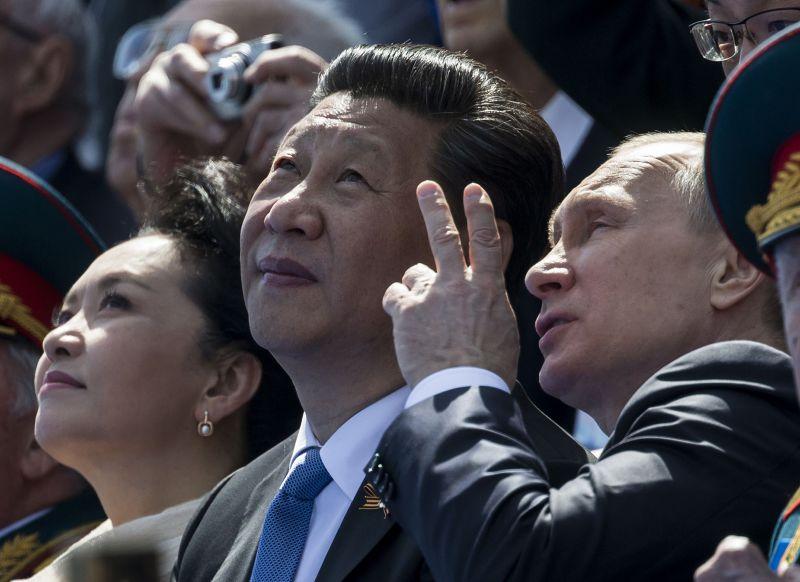 空中分列式時,普京與習近平交頭接耳。(美聯社)