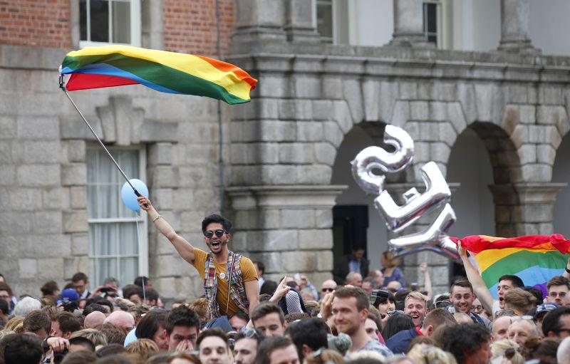 愛爾蘭民眾高舉彩虹旗慶賀。(美聯社)