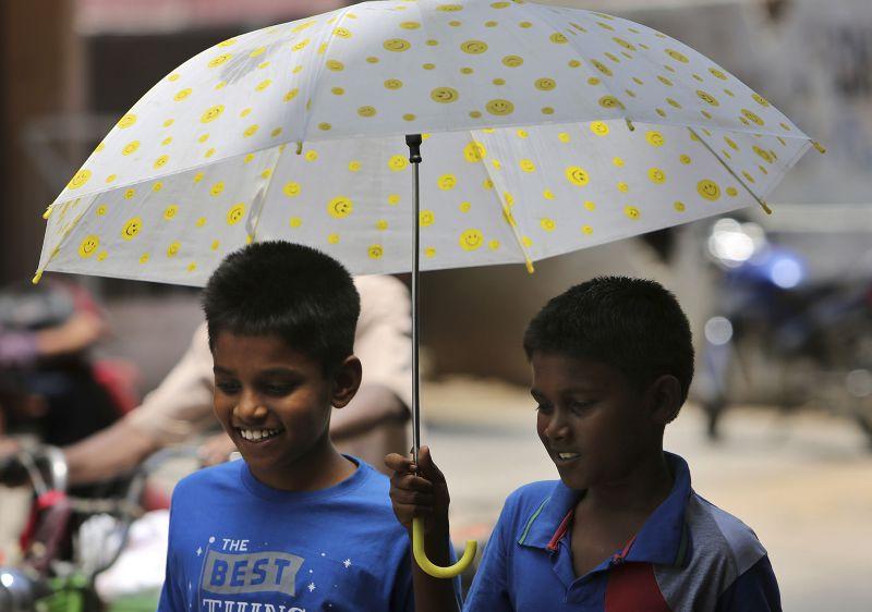 印度學童撐傘。(美聯社)