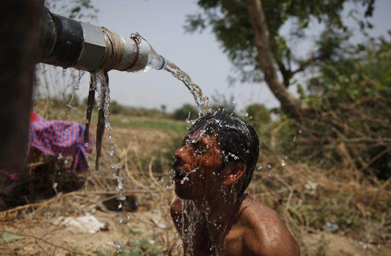 受不了高溫的印度民眾於路旁沖水降溫。(美聯社)