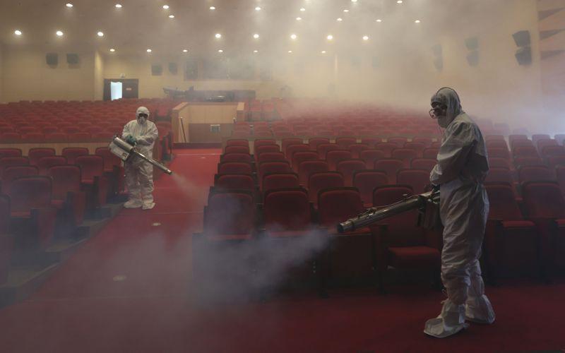 南韓檢疫人員在戲院中噴灑消毒。(美聯社)