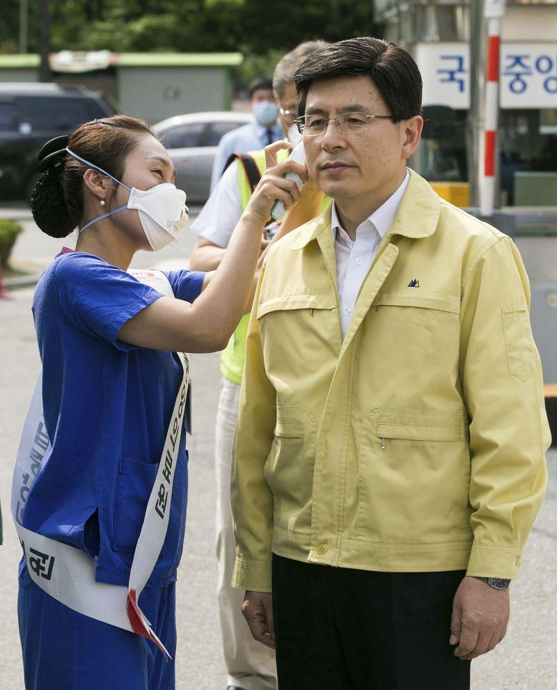 總理黃教安(右)19日視察醫院前,讓醫護人員先量耳溫。(美聯社)