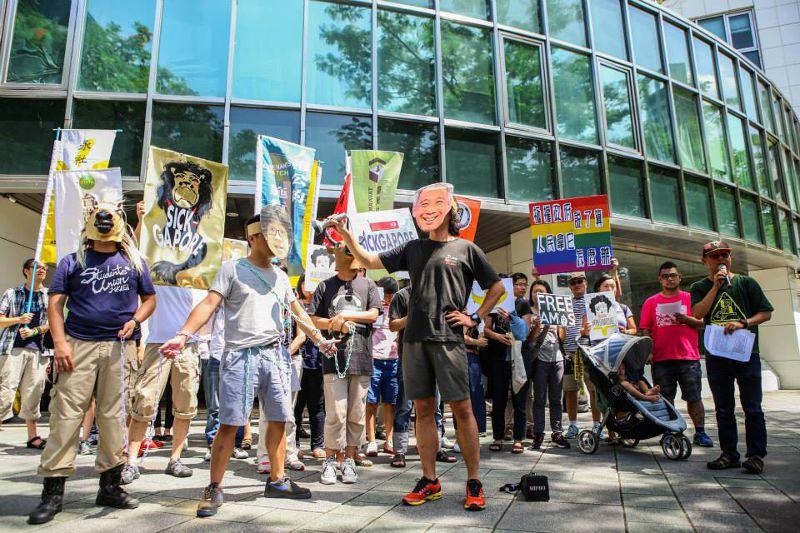 民團演出行動劇,頭戴現任新加坡總理李顯龍的面具,手拿著燈光照射被鐵鍊囚禁的Amos Yee,重現Amos Yee在精神病院遭受的不人道待遇。(取自台灣人權促進會網站)