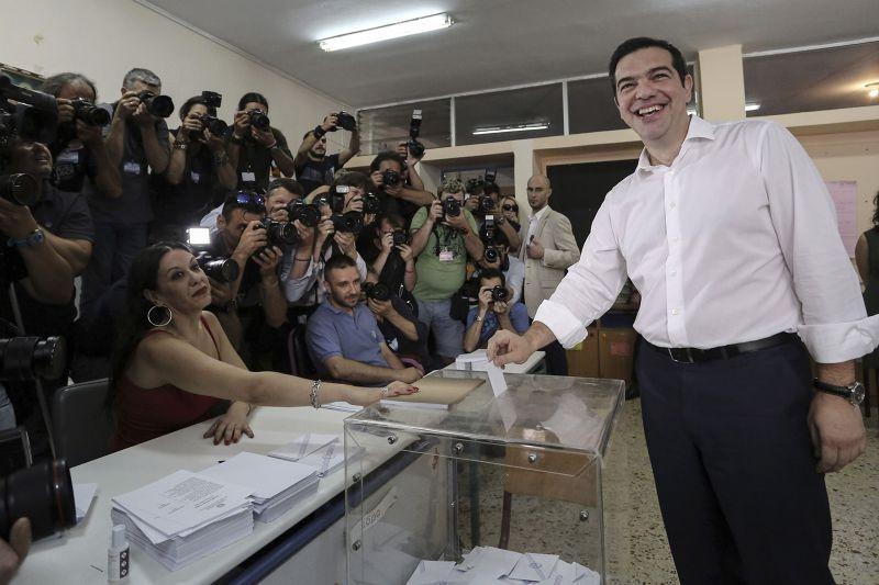 希臘總理齊普拉斯(右)5日前往投票。(美聯社)
