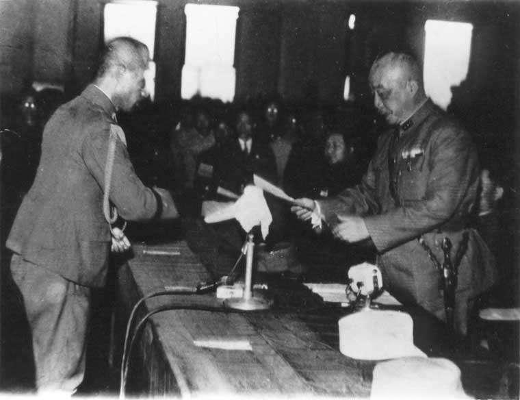 陳儀將軍於台北公會堂接受日軍第10方面軍參謀長諫山春樹將軍簽署過後的投降書。(維基百科)