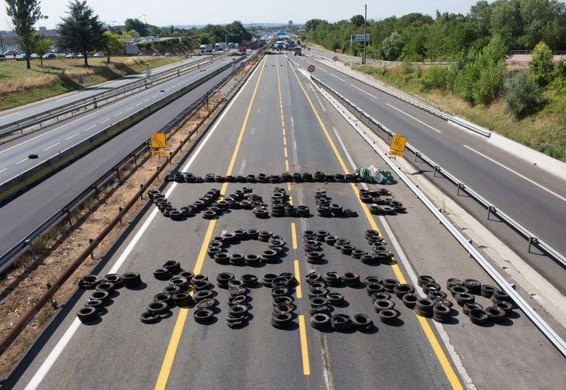 法國農民23日利用輪胎在高速公路上排出「瓦爾(總統),我們等你」。(美聯社)