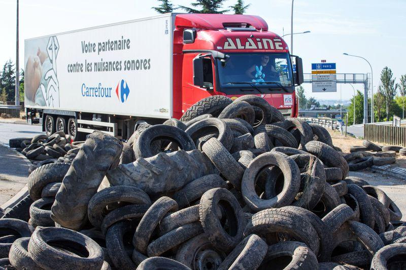 法國農民23日利用輪胎製作路障。(美聯社)