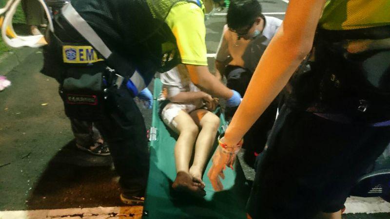 年輕女學生在突圍行動後左大腿受傷,包紮後坐上擔架,由醫療人員照顧。(林彥呈攝)