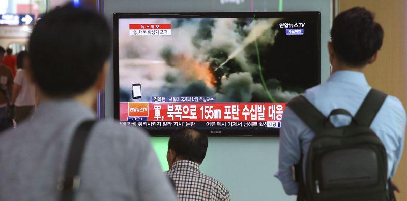 南韓人民20日觀看電視播放南韓還擊北韓砲擊畫面。(美聯社)