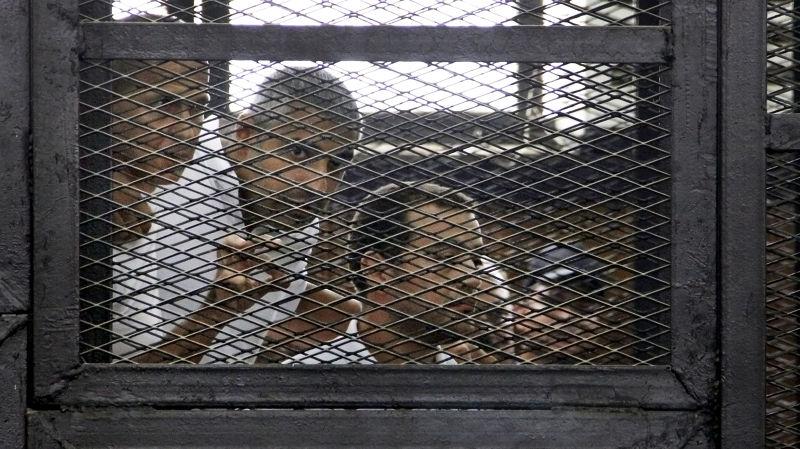 2014年6月在鐵籠中聆聽判決的三位記者(美聯社)。