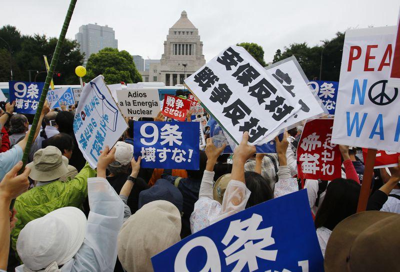 日本民眾冒雨包圍國繪,反對新安保法案。(美聯社)