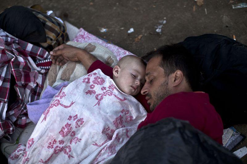 帶著襁褓幼兒逃難的難民席地而睡。(美聯社)