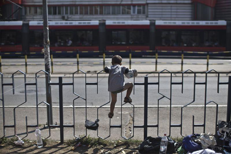 企圖爬越邊界圍牆的敘利亞幼童。(美聯社)