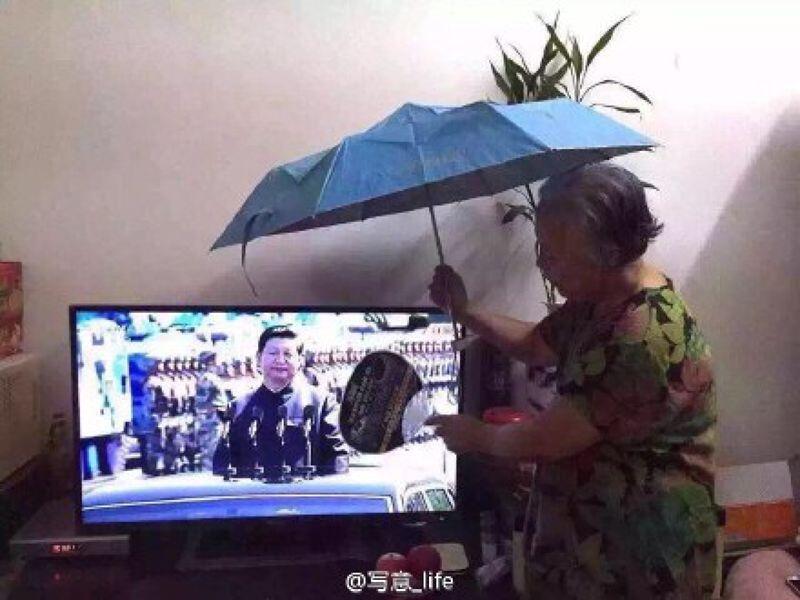 老奶奶替電視裡的習近平撐傘(取自微博)。