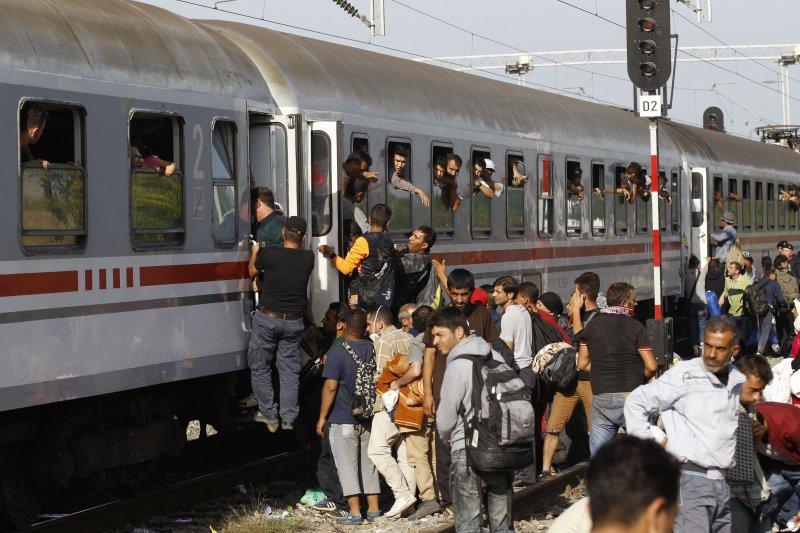 克羅埃西亞的敘利亞難民18日爭相進入火車。(美聯社)