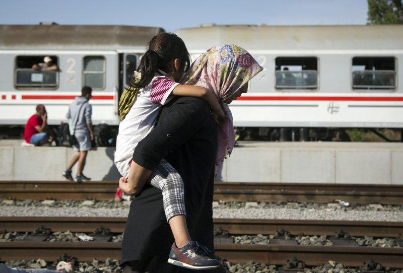 搭不上火車的難民徒步行走。(美聯社)
