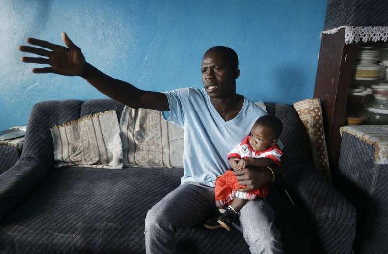 獅子山第三大城肯內馬(Kenema)的1位公衛人員抱著他領養的伊波拉孤兒(美聯社)