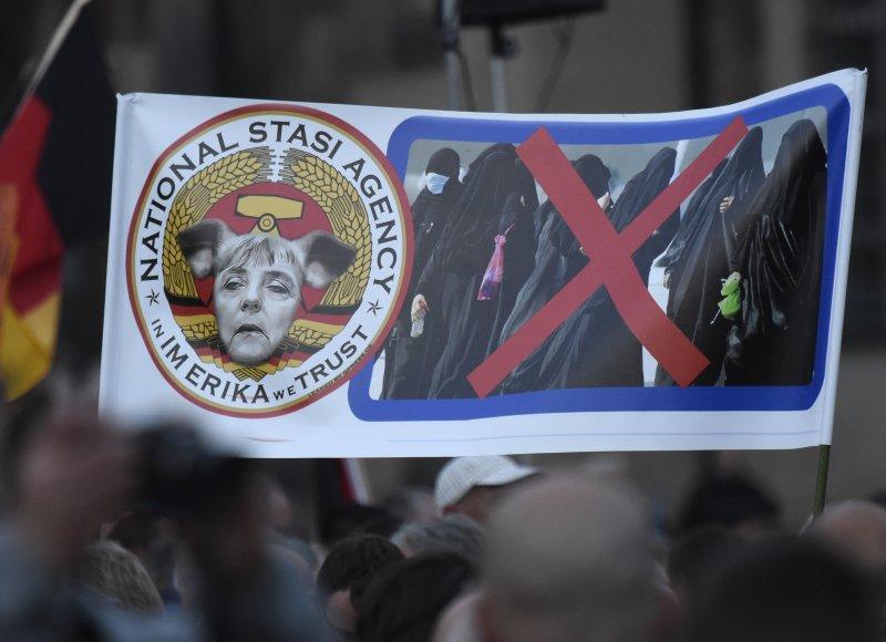 德國德勒斯登反梅克爾難民政策的民眾,高舉將梅克爾醜化為豬的抗議布條。穆斯林的照片也被打了一個大大的叉。(美聯社)