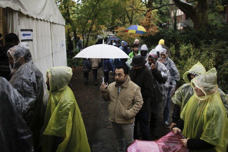 難民/移民在帳篷前排隊領取食物(美聯社)