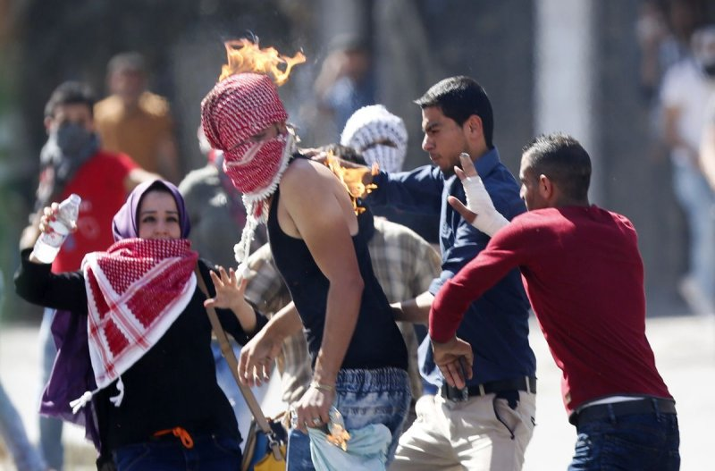 巴勒斯坦青年以石塊攻擊以色列士兵與居民(美聯社)