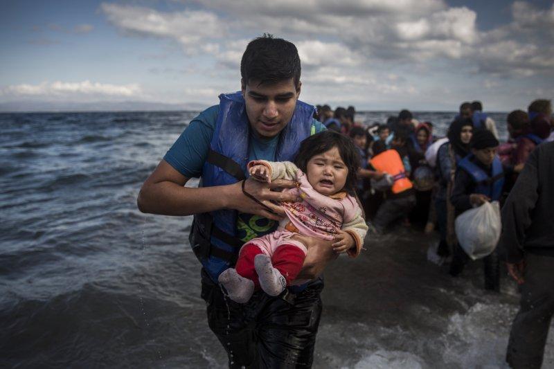 難民船抵達希臘莱斯沃斯島,救援人員抱起一名女童(美聯社)